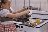 Girl Preparing Breakfast in Kitchen Valokuvavedos tekijänä William P. Gottlieb