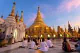 Shwedagon Paya (Pagoda) at Dusk with Buddhist Worshippers Praying Reproduction photographique par Lee Frost