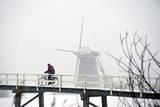 A Lone Cyclist Passes a Windmill in Kinderdijk Fotografie-Druck von Robert Vos