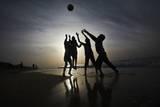 Palestinians Children Play Football at Al-Nusirat's Beach in Gaza Strip Fotografie-Druck von Ali Ali