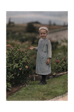 An Amish Girl Stands in a Garden Photographic Print by J. Baylor Roberts