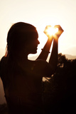 A Woman Captures the Sun in Her Hands Reproduction photographique par Chris Bickford