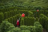 Balloons Drift Away from a Young Woman in the Garden Maze at Luray, Virginia Lámina fotográfica por Sartore, Joel