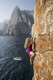 Watched by a Teammate, a Climber Scales a Cliff Rising from the Gulf of Oman Fotografie-Druck von Jimmy Chin