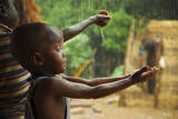 A Bassari Child Holding Out Hands to Collect Rainwater, Bassari Country, East Senegal Fotografisk tryk af Enrique Lopez-Tapia