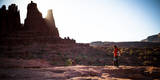 A Male Hiker Enjoys the Rising Sun's Warmth at Fisher Towers in Moab, Utah Photographic Print by Dan Holz