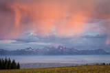 Sunrise Illuminates a Rain Shower Above a Smoke-Covered Jackson Hole, Wyoming Impressão fotográfica por Mike Cavaroc