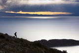 A Man Walks Along a Rocky Crest Above Lake Titicaca in Bolivia During Sunset Reproduction photographique par Sergio Ballivian