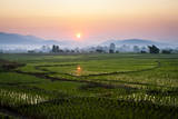 The Sun Sets Behind Foggy Hills and Expansive Rice Paddy Fields Near Chiang Mai, Thailand Photographic Print by Dan Holz