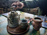 A Hand on a Teapot and Yerba Mate at Refugio Piltriquitron in the Andes of Patagonia, Argentina Fotografisk trykk av Maureen Eversgerd