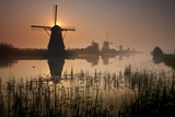 Sunset and Silhouetted Windmills Reflected in the Canals Kinderdijk Photographic Print by Darrell Gulin