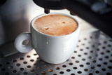 White Ceramic Cup of Fresh Espresso with Foam in the Coffee Machine. Photographic Print by Eugene Sergeev
