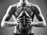 Close-Up of Topless Man Holding Rugby Ball in Isolation Reproduction photographique par  pressmaster
