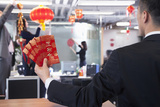Businessman Holding Red Envelopes and Coworkers Hanging Decorations for Chinese New Year Fotografisk trykk av  XiXinXing