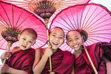 Myanmar, Mandalay Division, Bagan. Portrait of Three Novice Monks under Red Umbrellas (Mr) Fotografisk trykk av Matteo Colombo