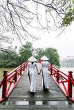 Vietnam, Hanoi, Hoan Kiem Lake. Walking on Huc Bridge in Traditional Ao Dai Dress Photographic Print by Matteo Colombo