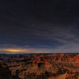 The Grand Canyon on a Moonlit Night. Saint George City, Utah, Illuminates Clouds on the Left Fotografisk tryk af Babak Tafreshi
