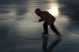 A Girl in Silhouette Skating on a Frozen Lake Photographic Print by Peter Mather