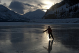 A Silhouetted Girl Skating on a Frozen Mountain Lake Photographic Print by Peter Mather