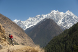 A Mountain Biker Cycles Along a Trail in the Tsum Valley in Nepal Fotografie-Druck von Alex Treadway
