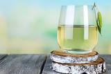 Glass of Fresh Birch Sap on a Wooden Table on Nature Background Valokuvavedos tekijänä Africa Studio