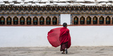 A Young Monk Walking Through a Monastery Fotografisk trykk av Michael Melford