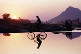 Bicyclist Crossing Shallow River at Sunset with Women in Background Doing Washing Stampa fotografica di  Design Pics Inc