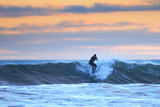 A Surfer Rides a Winter Wave Off the Coast of Maine at Sunset Stampa fotografica Premium di Robbie George