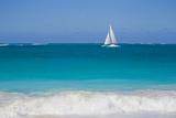 Surf Surges onto a Beach as a Sailboat Passes Offshore Lámina fotográfica por Mike Theiss
