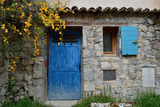 A Stone Building with a Bright Blue Door and Window Shutter 写真プリント : Keith Ladzinski