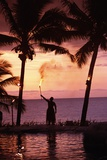Native in a Grass Skirt Holding a Flaming Torch by Coast at Sunset Reproduction photographique par  Design Pics Inc
