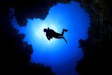 Scuba Diver Swims over Underwater Cave, Silhouette against Sun Fotografie-Druck von Rich Carey