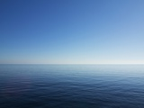 Blue Sky over Calm Sea Photographic Print by Norbert Schaefer