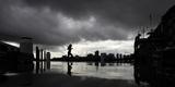 A Lunch-Hour Jogger Runs Along a Harbourside Wharf as a Thunderstorm Breaks over Central Sydney Fotografisk tryk af TIM WIMBORNE