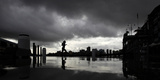 A Lunch-Hour Jogger Runs Along a Harbourside Wharf as a Thunderstorm Breaks over Central Sydney Photographic Print by TIM WIMBORNE