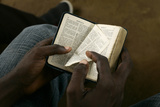 Boy Turns a Page of a Bible During a Mass at the Simulambuco Church in Cabinda Fotografisk tryk af Rafael Marchante
