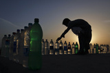 A Boy Is Silhouetted Against the Setting Sun While Arranging Bottles of Drinking Water in Karachi Reproduction photographique par Akhtar Soomro