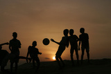 Children Playing Soccer are Silhouetted at Sunset in Nigeria's Main City of Lago Lámina fotográfica por George Esiri