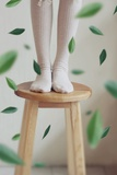 Young Woman Feet in Socks on a Stool Photographic Print by Carolina Hernandez