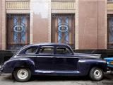 Vintage Car Parked Next to the Bacardi Rum Building in Havana, Cuba Photographie par Carol Highsmith