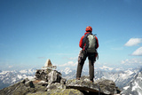 A Climber Stands at the Summit of a Mountain Overlooking the Mountains of Glacier National Park Photographic Print by Michael Hanson
