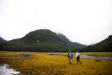 A Man and Woman Walk Along the Tidal Area of an Inlet in Remote Alaska Photographic Print by Michael Hanson