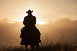A Cowboy on Horseback at Sunset, in a Pasture Stampa fotografica di Jak Wonderly