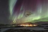 Aurora Borealis, the Northern Lights, Above the Lights of a Seaside Town in Iceland Fotografisk tryk af Babak Tafreshi