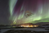 Aurora Borealis, the Northern Lights, Above the Lights of a Seaside Town in Iceland Photographic Print by Babak Tafreshi