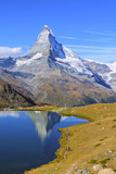 Hikers Walking on the Path Beside the Stellisee with the Matterhorn Reflected Fotografisk trykk av Roberto Moiola