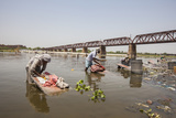 Women Wash Clothes in the Polluted Water of the Yamuna River Photographic Print by Roberto Moiola