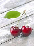A Pair of Cherries with a Leaf on a Wooden Table Photographic Print by Jürgen Klemme