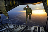 A U.S. Soldier Salutes His Fellow Soldiers While Jumping Out of a C-130 Hercules Photographic Print by  Stocktrek Images
