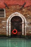 Doorway Along Canal with Safety Buoy Venice, Italy Foto av Darrell Gulin